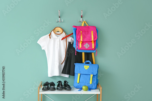 Fotografering Stylish school uniform with backpacks near color wall