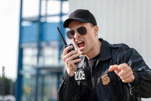 Fotografie, Obraz Aggressive police officer with two-way radio outdoors