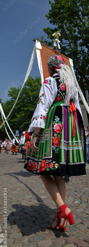 Fototapeta Woman in beautiful colorful folk costume from Lowicz region, Poland, while joins Corpus Christi procession