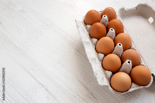 Raw Brown Eggs in a paper box, side view. Copy space.