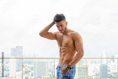 Young handsome muscular Persian man shirtless and looking down against view the Canvas Print