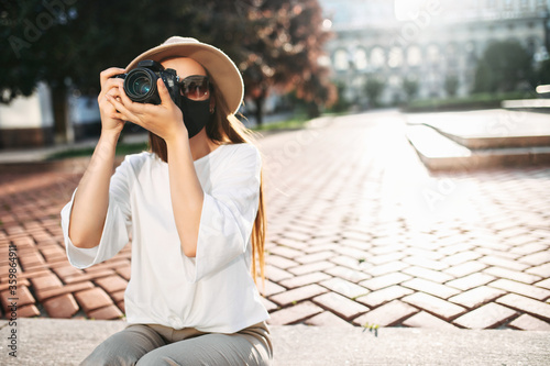 Fotografia, Obraz Close-up portrait of a girl photographer in hat with a protective medical mask o