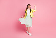 Full Length Photo Of Funky Lady Walk Down Street Good Mood Raise Green Long Wavy Skirt Wave Arm See Friends Wear Yellow Leather Jacket Sneakers Isolated Pastel Pink Color Background