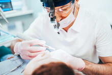 Dentist Cleans Tooth Canals Of...