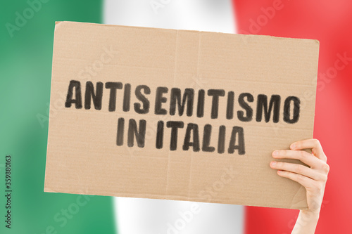 Photo The phrase  Antisemitism in Italy  in Italian language on a banner in men's hand with blurred flag on the background