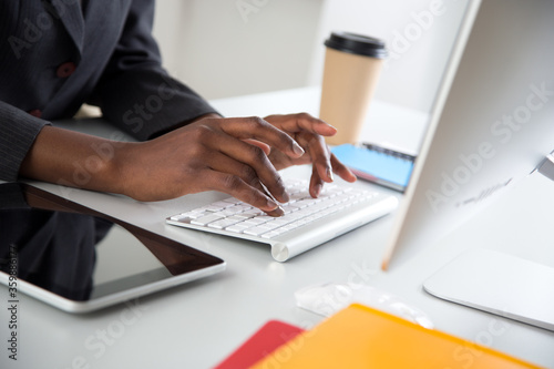 Fototapeta Close-up of hands of african-american businesswoman typing on a laptop. obraz