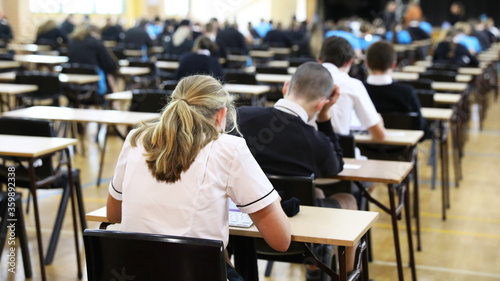 anonymous students in uniform sitting an exam online using digital tablets Slika na platnu