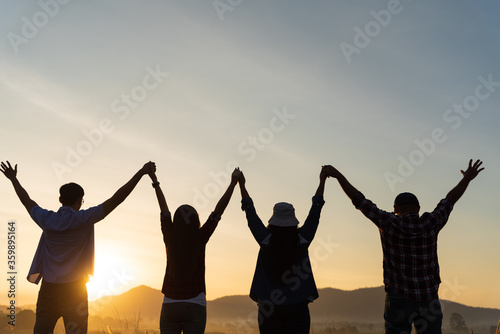 Obraz Group of happy friends are having fun with raised arms together in front of mountain and enjoy sunrise sunset showing unity and teamwork. Friendship happiness leisure partnership team concept. - fototapety do salonu