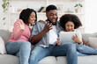 Cheerful African Family Having Fun With Digital Tablet At Home