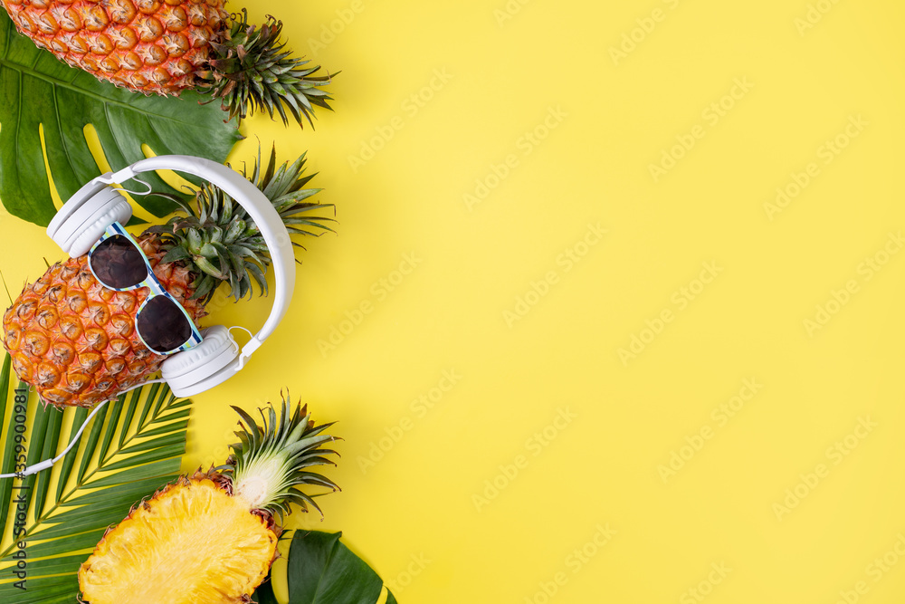 Fototapeta Funny pineapple wearing white headphone, listen music, isolated on yellow background with tropical palm leaves, top view, flat lay design concept.