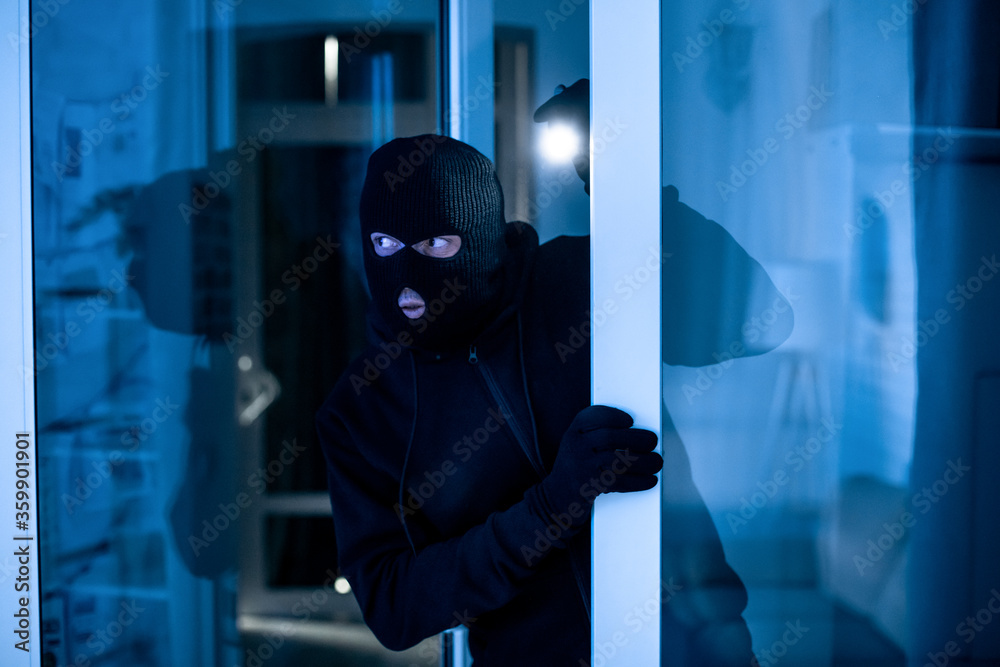 Fototapeta Intruder breaking into apartment or office to steal something