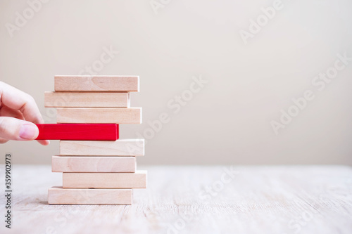 Fotografía Businessman hand placing or pulling red wooden block  on the tower