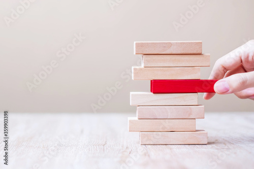 Cuadros en Lienzo Businessman hand placing or pulling red wooden block  on the tower