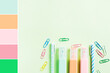 Pastel green back to school flat lay with colorful stationery - highlighters and clips. Color swatch