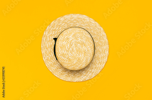 Fotografie, Obraz Women s summer straw hat on yellow background top view flat lay copy space