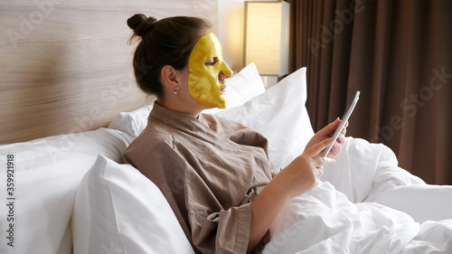 Leinwand Poster brunette lady with golden face mask surfs internet with tablet resting in soft b