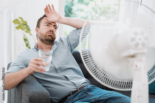 Leinwand Poster Man refreshing with electric fan against summer heat wave