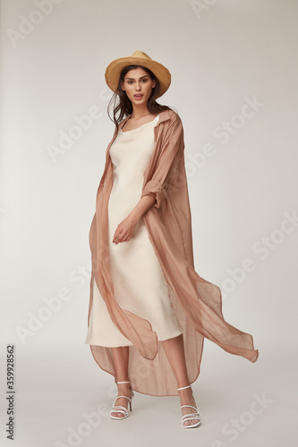 Beautiful woman fashion model makeup brunette hair perfect body shape tanned skin wear clothes summer collection organic silk dress and long shirt cape stylish sandals shoes, accessory hat romantic Wallpaper Mural