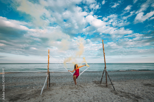 Fotografie, Obraz Vacanze in Calabria con mare e ragazza seduta sull'altalena