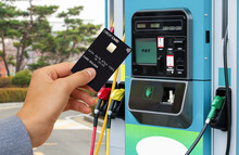 Hand With A Credit Card On The Background Of A Self-service Gas Station. Contactless NFC Payment