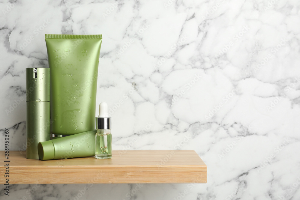 Fototapeta Set of cosmetic products on wooden shelf near white marble wall, space for text