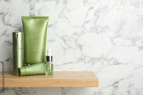 Set of cosmetic products on wooden shelf near white marble wall, space for text