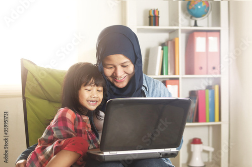 Asian muslim mom and little baby girl daughter learning online or watching video Canvas