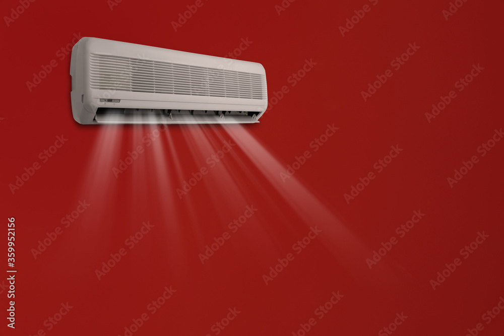 Modern air conditioner on red wall indoors