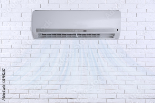 Photo Modern air conditioner on white brick wall indoors