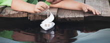 White Toy Boat In Child Hand A...