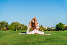 Woman Doing Yoga On A Mat On Lawn