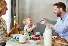Smeared Little Boy With His Parents At Breakfast Table