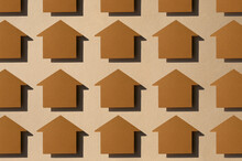 Pattern Of Rows Of House Shaped Paper Cuts Against Brown Background