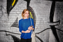 Young Woman Using Smart Phone While Standing Against Graffiti Wall At Night