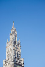 Germany, Bavaria, Munich, Low Angle View Of New Town Hall Clock Tower Standing Against Clear Blue Sky