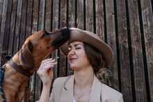 Portrait Of Woman With Hat And Her Sniffing Dog