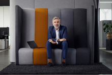 Portrait Of Mature Businessman Sitting On Couch In Office