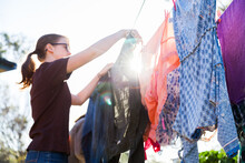 Sun Flare Through Clothes On Washing Line With Person Pegging Shirt
