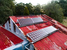 Solar Panels On Red Tin Roof Of Shed Building On Off Grid Farm