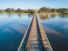 Looking Down Railway Tracks On Top Of A Bridge Across A Lake