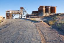 A Road Leading Up To Rusted Tanks And Abandoned Buildings Of An Closed Mine