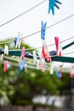 Blue Pink And White Plastic Clothes Pegs On A Washing Line