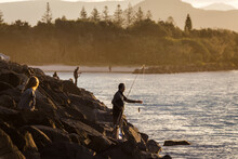 Fisherman Standing On Rocks Be...
