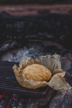 Rustic Damper Bread In Brown Baking Paper On The Red Hot Coals Of A Campfire