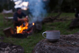 Close up of tea with man tending to campfire in background on rural property