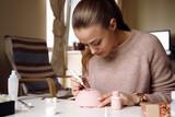Focused woman painting handmade Christmas ornament