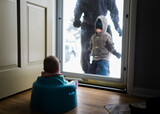 baby sits in entryway watching dad and brother