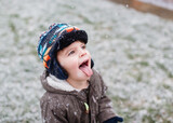 little boy catches snowflakes on tongue