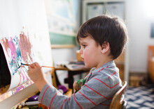 Child Paints At Easel