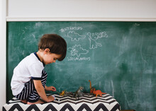 Boy Traces Dinosaurs On Chalkboard
